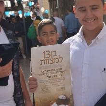 ילד מחזיק בתעודת בר מצווה שלו