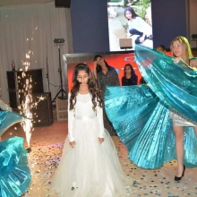 ילדה בבת מצווה שלה עומדת באולם ומסביבה שתי רקדניות רוקדות